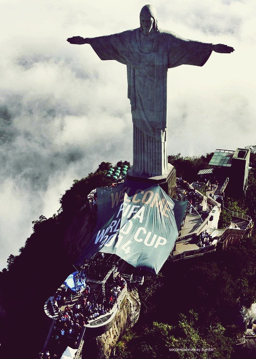 The statue of Christ the Redeemer atop Corcovado mountain overlooks a banner that reads 'Welcome FIFA World Cup 2014'  in Rio de Janeiro